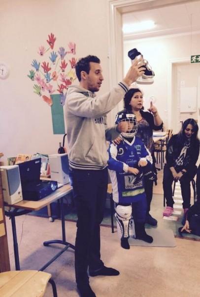 Rickard Wallin Kamperin visar barnen på Kumlienskolan vad som ingår i en bandyutrustning.